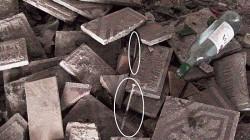 Due siringhe utilizzate da tossicodipendenti e pericolosamente  abbandonate tra mattonelle e bottiglie di vetro